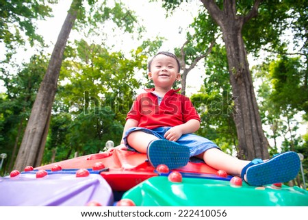 Portrait of happy asian kid outdoor in spring park looking at camera. He has lots of fun. Happy child playing at a playground. - stock photo