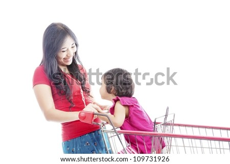 Portrait of happy asian mother laughing with her daughter on the shopping cart. Isolated on white - stock photo