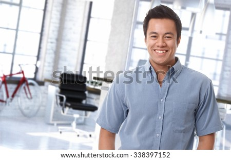Portrait of happy asian office worker at trendy workplace. - stock photo