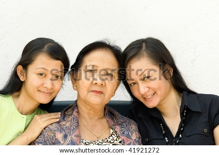 portrait of happy asian women generation of mother and two daughter posing together - stock photo