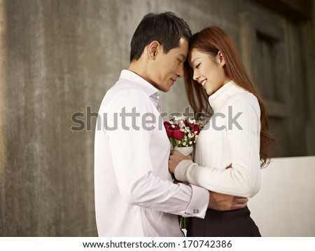 portrait of happy asian young lovers with flowers. - stock photo