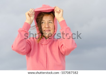 Portrait of happy attractive looking middle aged woman wearing pink sweater, standing outdoor at beach, isolated with storm clouds and ocean as background and copy space. - stock photo