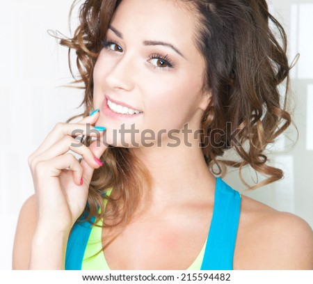 Portrait of happy attractive young brunette woman with colorful nails - stock photo