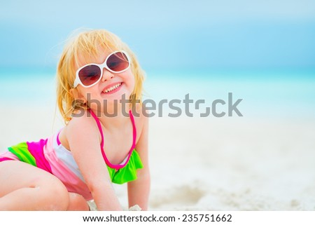 Portrait of happy baby girl in sunglasses on beach - stock photo