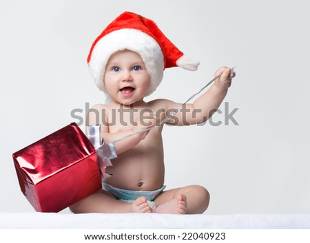 Portrait of happy baby wearing Santa cap and unwrapping Christmas present - stock photo