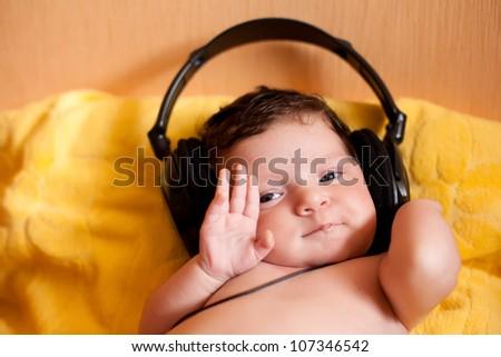Portrait of happy baby with headphones - stock photo