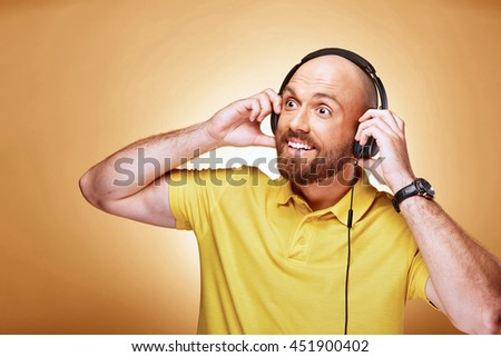 Portrait of happy bald bearded man with earphones and watch