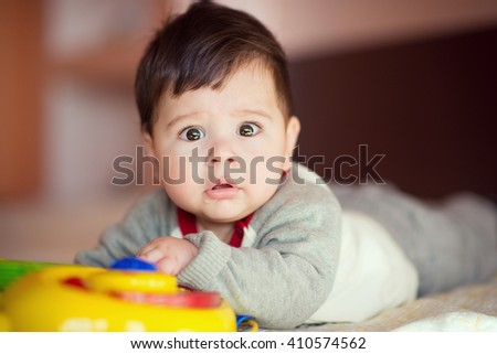 Portrait of happy beautiful baby on the bed in his room. - stock photo