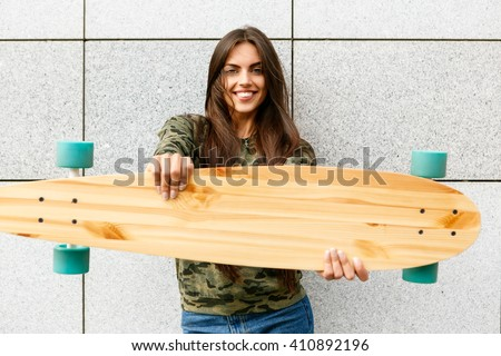 Portrait of happy beautiful brunette girl with long sexy healthy hair hold her wooden longboard skateboard in front of her, look to the camera and smile. Urban scene, city life. Hipster cute lady. - stock photo