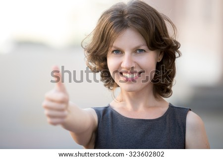 Portrait of happy beautiful business woman posing on the street in summer, friendly smiling, looking at camera with cheerful confident expression, showing thumbs up, focus on face - stock photo