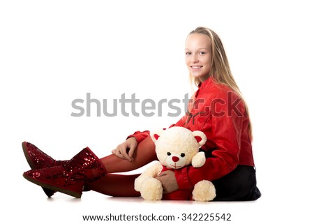 Portrait of happy beautiful casual teenage girl in red leather jacket sitting with teddy bear, friendly smiling, looking at camera with cheerful expression, studio, white background, copy space - stock photo