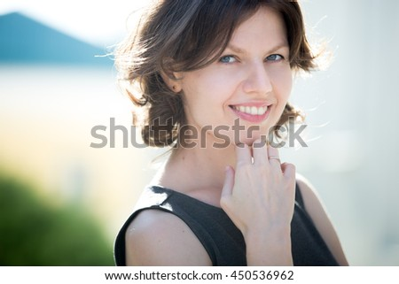Portrait of happy beautiful caucasian woman on the street in summer, friendly smiling, looking at camera with cheerful confident expression - stock photo