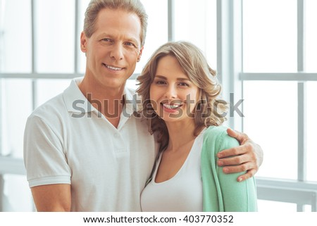 Portrait of happy beautiful couple in casual clothes cuddling, looking at camera and smiling - stock photo