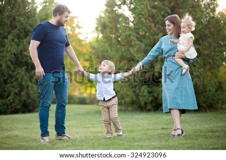 Portrait of happy beautiful family of four walking in park. Mom, dad and two siblings enjoying leisure time in summer, talking, playing, having fun together - stock photo