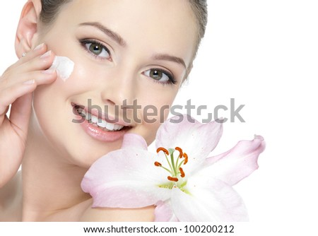 Portrait of happy beautiful girl with lily applying  cream - isolated on white.