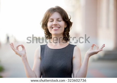 Portrait of happy beautiful office woman meditating on urban street in summer, smart casual businesswoman practicing yoga outdoor holding hands in mudra, smiling with enjoyment, breathing fresh air - stock photo