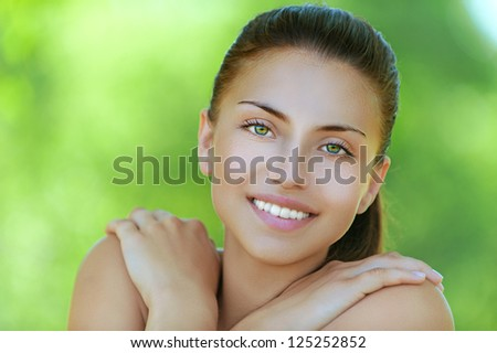 Portrait of happy beautiful young woman, against background of summer green park.