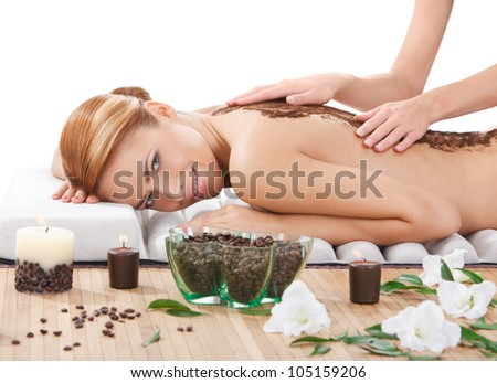 portrait of happy beautiful young woman getting back massage with coffee scrub at spa