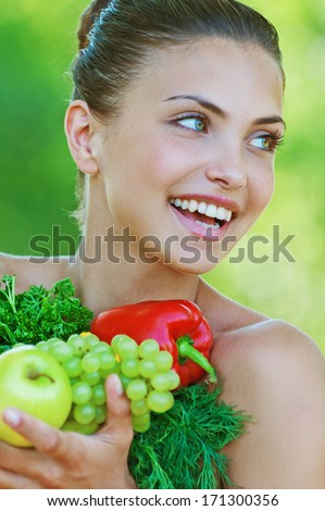 Portrait of happy beautiful young woman with vegetables, against background of summer green park. - stock photo