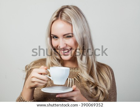 Portrait of happy blond winking woman holding white cup - stock photo