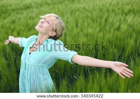 Portrait of happy blonde woman at the Greenfield - stock photo