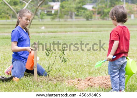 Portrait of Happy Boy and Girl Watering Plants Outdoors - stock photo