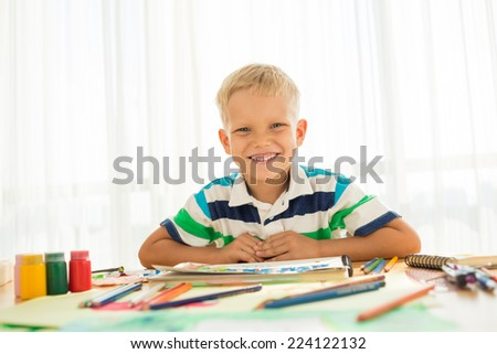 Portrait of happy boy at his table looking at the camera - stock photo