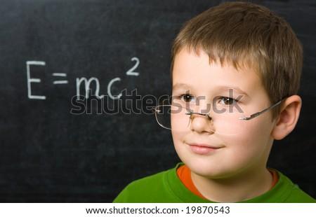 Portrait of happy boy before blackboard - stock photo