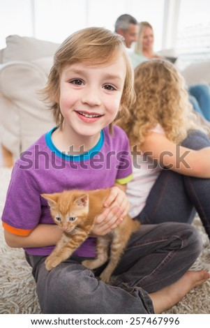 Portrait of happy boy holding kitten while sitting with family in living room