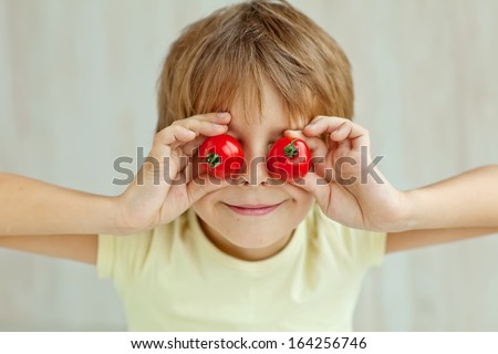Portrait of happy boy holding ripe tomatoes before his eyes