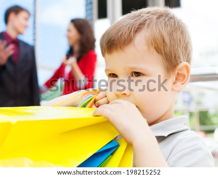 Portrait of happy boy holding shopping bags with his parents behind - stock photo