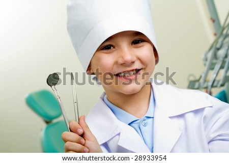 Portrait of happy boy in medical uniform holding dentistry tools in hand - stock photo