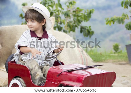 Portrait of Happy Boy in Old Car Having Fun Outdoors - stock photo