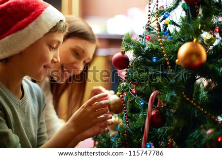Portrait of happy boy in Santa cap decorating Christmas tree - stock photo