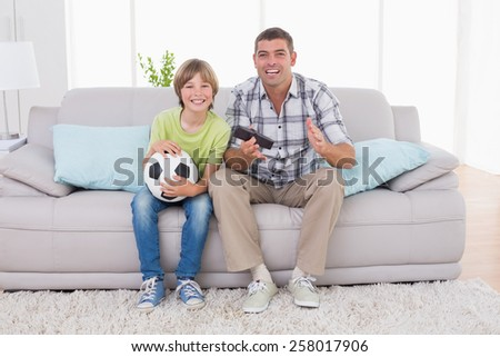 Portrait of happy boy watching soccer match with father on sofa at home - stock photo