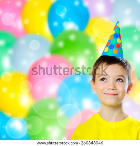 Portrait of happy boy with birthday cap on abstract colorful balloons background - stock photo