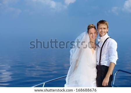 Portrait of happy bride and groom on a yacht - stock photo