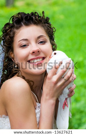 Portrait of happy bride holding white dove and cuddling it up to her cheek while looking at camera