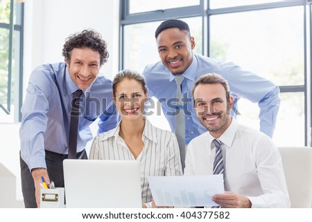 Portrait of happy business colleagues reviewing a report at desk in office
