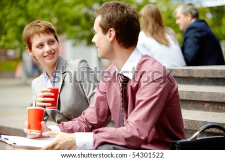 Portrait of happy business partners chatting during break outside at summer - stock photo