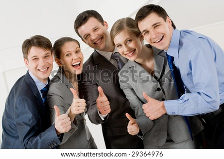 Portrait of happy business partners looking at camera with smiles and showing sign of okay - stock photo