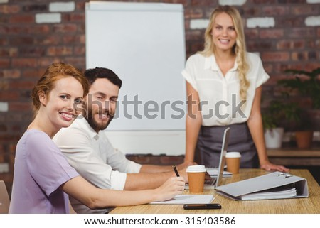 Portrait of happy business people during presentation in creative office - stock photo