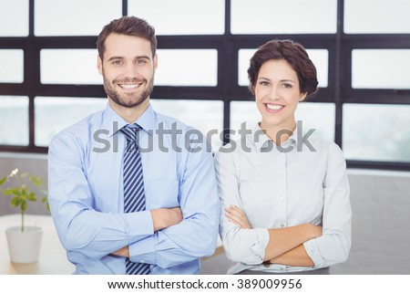 Portrait of happy business people with arms crossed standing in office - stock photo