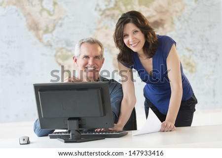 Portrait of happy business people working at office desk with world map in background - stock photo