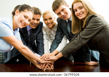 Portrait of happy business team keeping their hands on top of each other - stock photo