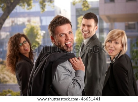 Portrait of happy business team standing outdoor having fun, sticing out their tongues. - stock photo