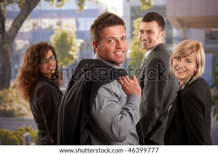 Portrait of happy business team standing outdoor looking back, smiling. - stock photo