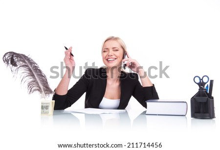 Portrait of happy business woman sitting on her desk. beautiful young woman laughing at table and talking on cell phone - stock photo