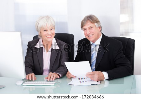 Portrait Of Happy Businessman And Businesswoman Working With Computer At Desk - stock photo