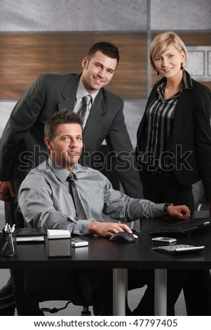 Portrait of happy businessman and team at office desk, looking at camera, smiling. - stock photo
